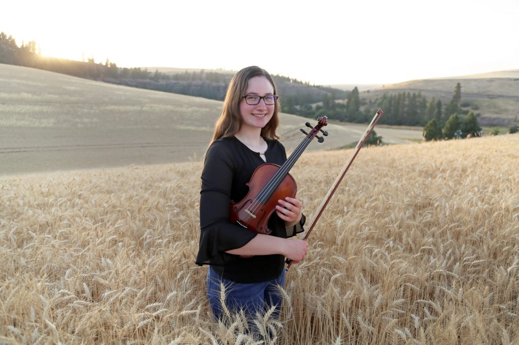 Kyra Harris in a wheat field with a violin